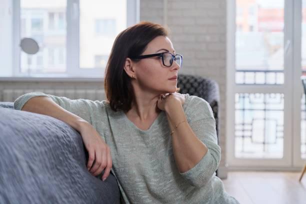 Mujer madura deprimida sentada en el suelo en casa - foto de stock