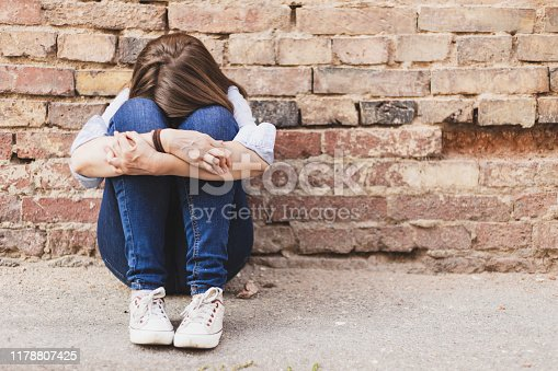 Scared millennial girl sitting alone in the city next to a brick wall - Casually dressed young woman wearing jeans hiding outdoors - Insecure female having panic attack