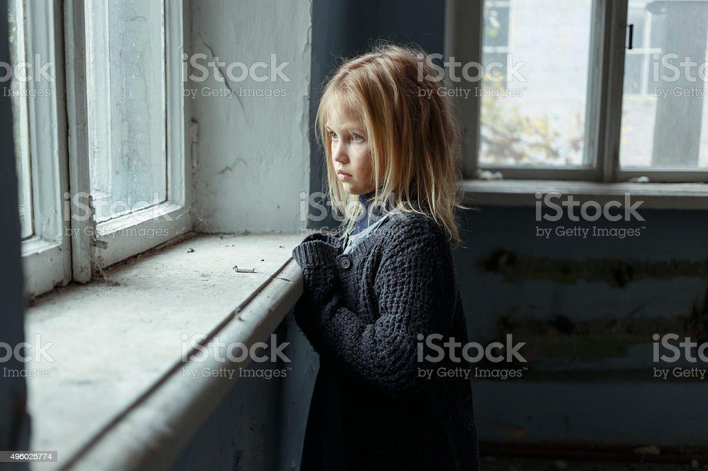 Ein deprimierter poot Mädchen steht in der Nähe vom Fenster nachdenkt. – Foto