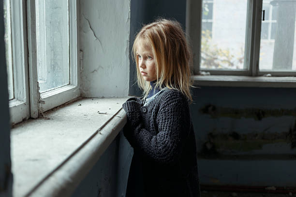 depressed poot girl standing near window - poverty stock pictures, royalty-free photos & images