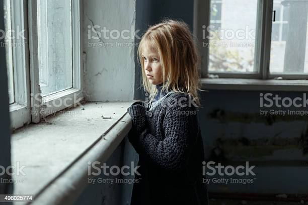 Hopeless life. Close up of depressed poor little girl standing near window and looking aside while feeling miserable
