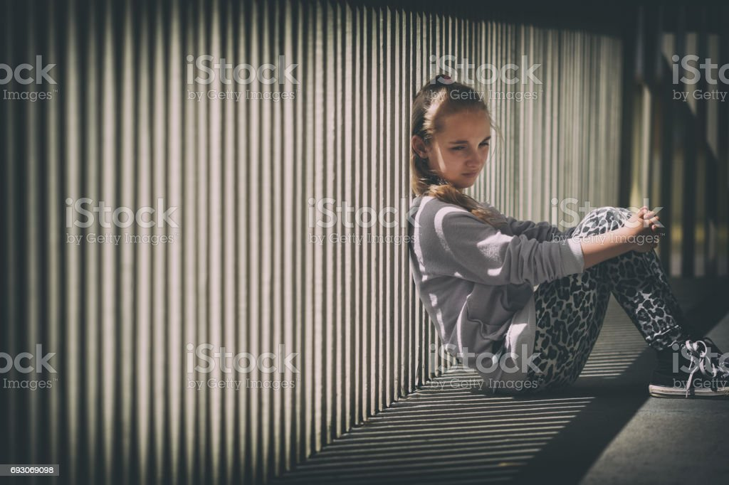 Depressed Preteen Girl Sits Against Railing stock photo