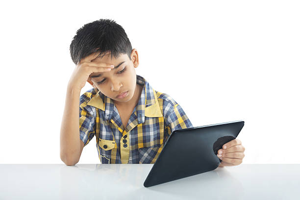 Depressed School boy with tablet stock photo