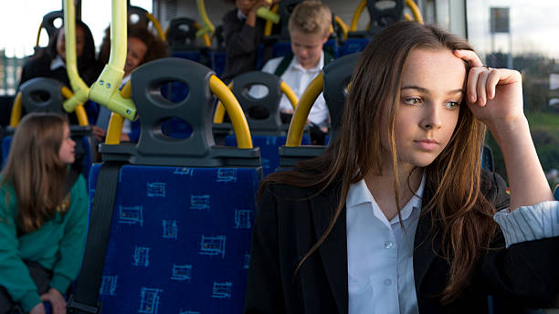 Depressed Schoolgirl Sitting Alone on Bus stock photo