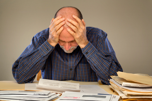 istock Depressed Senior Adult Man With Stacks of Papers and Envelopes 168763161