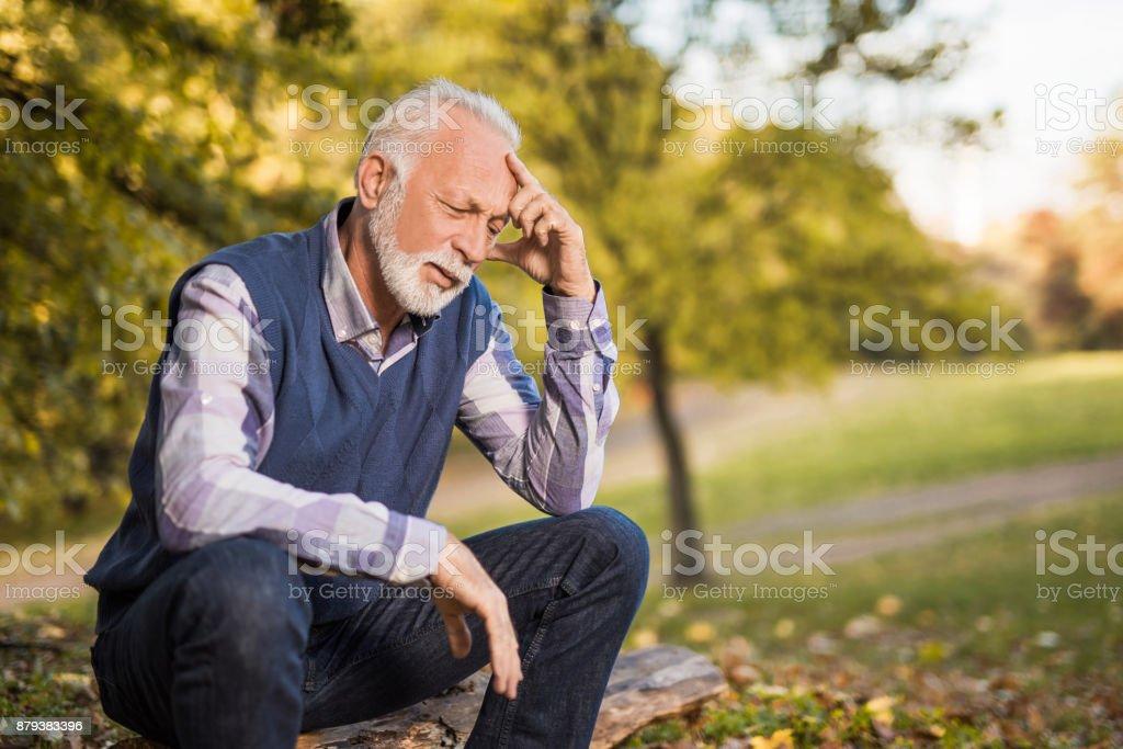 Depressed senior man feeling emotions of regret and having health problems. stock photo