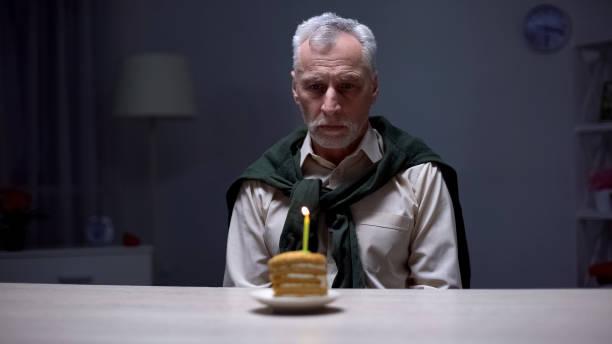 depressiver senior mann blickauf geburtstagstorte, feiert urlaub allein zu hause - geburtstag vergessen stock-fotos und bilder