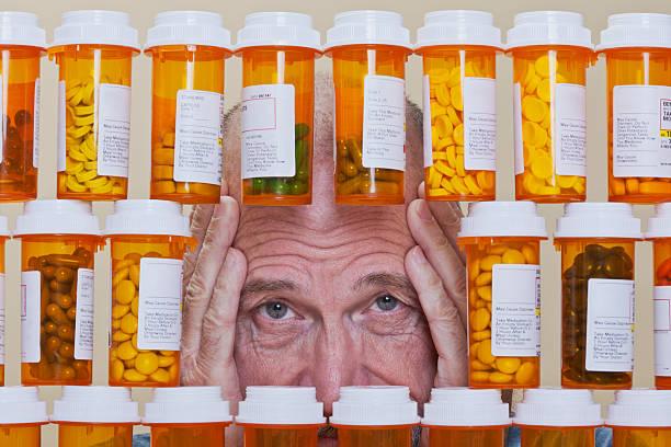 Ein deprimierter Senior Mannes Blick durch die Reihen von verschreibungspflichtigen Medikamenten – Foto