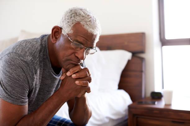 depressieve senior man op zoek ongelukkig zittend aan de zijkant van bed thuis met hoofd in handen - dementia stockfoto's en -beelden