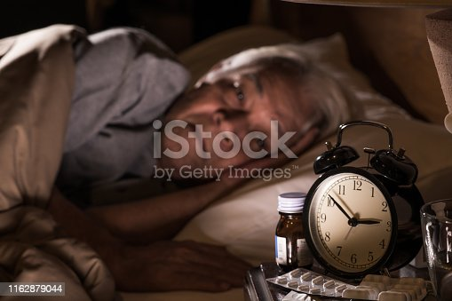 istock A depressed senior man lying in bed cannot sleep from insomnia 1162879044
