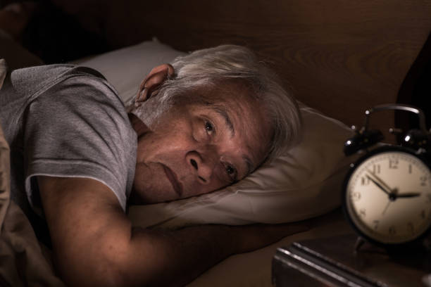 A depressed senior man lying in bed cannot sleep from insomnia A depressed senior man lying in bed cannot sleep from insomnia only senior men stock pictures, royalty-free photos & images
