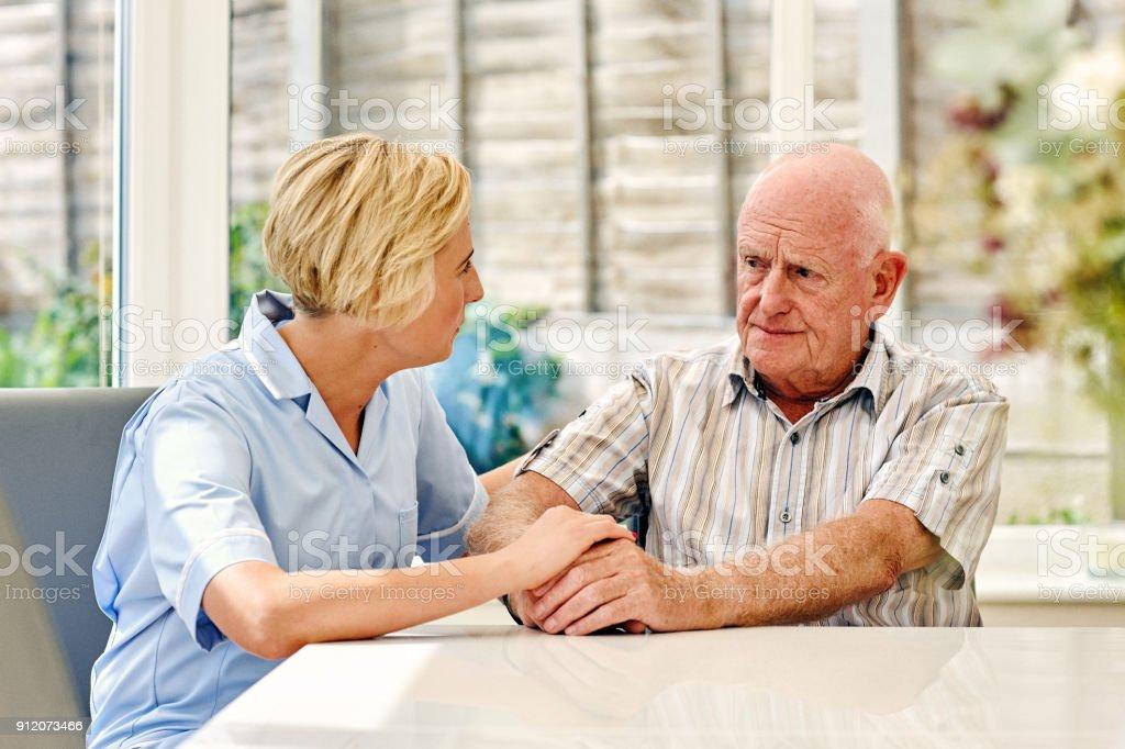 Deprimiert senior Mann, sitzend mit weiblichen Betreuungsperson – Foto