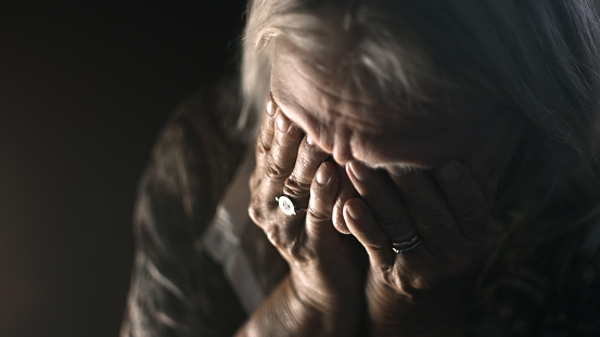 Desperate senior crying in a dark room. Perfectly usable for a wide range of topics like depression, loneliness or mental health in general.