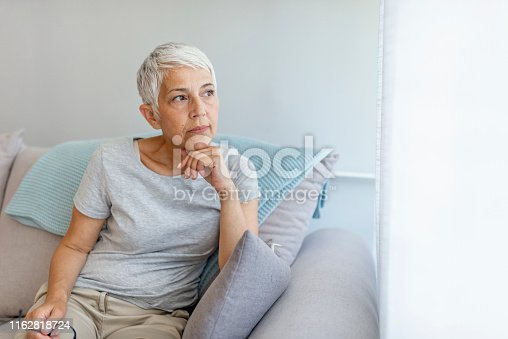 istock Depressed senior woman at home 1162818724