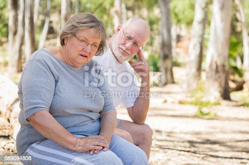 istock Depressed Senior Woman Sits With Concerned Husband Outdoors 589094808