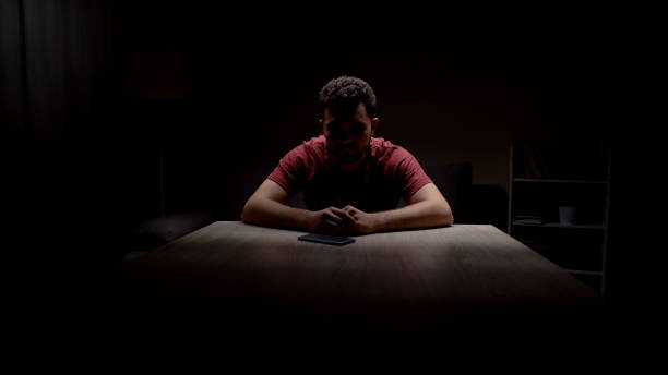 Depressed single man sitting in dark room looking at phone, waiting for call Depressed single man sitting in dark room looking at phone, waiting for call ignorance stock pictures, royalty-free photos & images