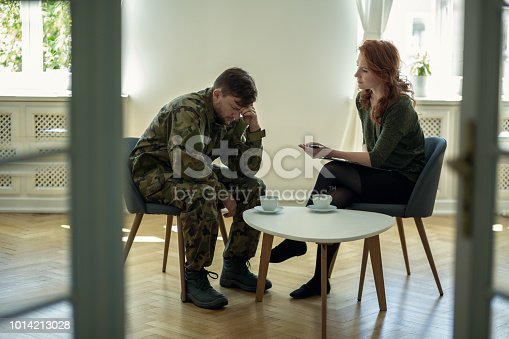 istock Depressed soldier and his psychotherapist during a session. View through a door 1014213028