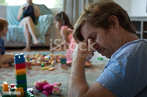 istock Depressed stressed out father at home with his kids and wife. 1252819542