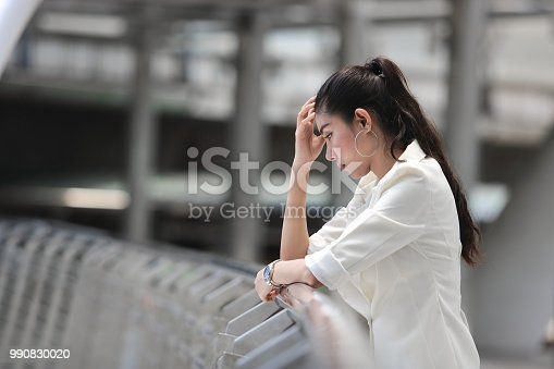 istock Depressed stressed young Asian business woman with hands of face suffering from trouble 990830020