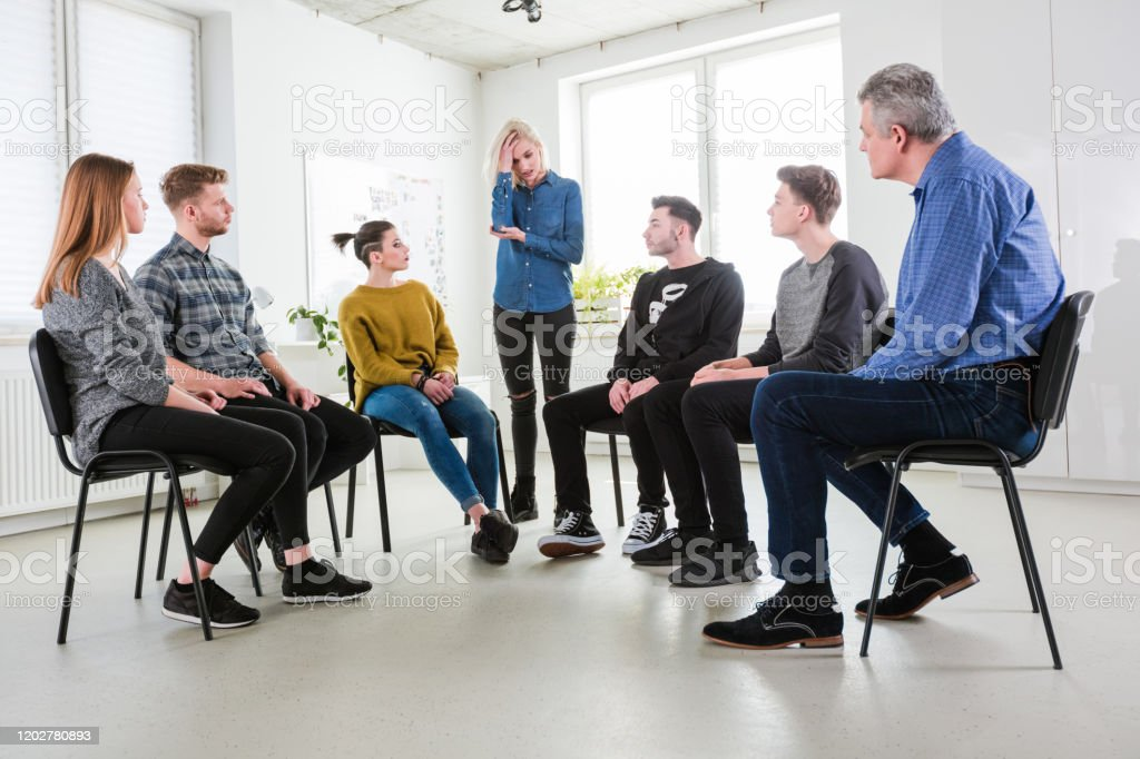 Depressed student sharing problems in meeting Depressed female student sharing problems during meeting. Men and women are wearing casuals in lecture hall. They are in group therapy at university. 18-19 Years Stock Photo