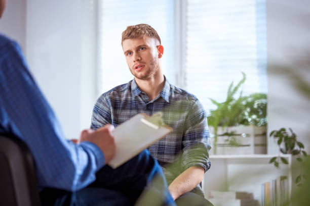 Depressed student sharing problems with therapist University student sharing his problems with therapist. Young depressed male is sitting with mental health professional. They are in lecture hall. counseling stock pictures, royalty-free photos & images
