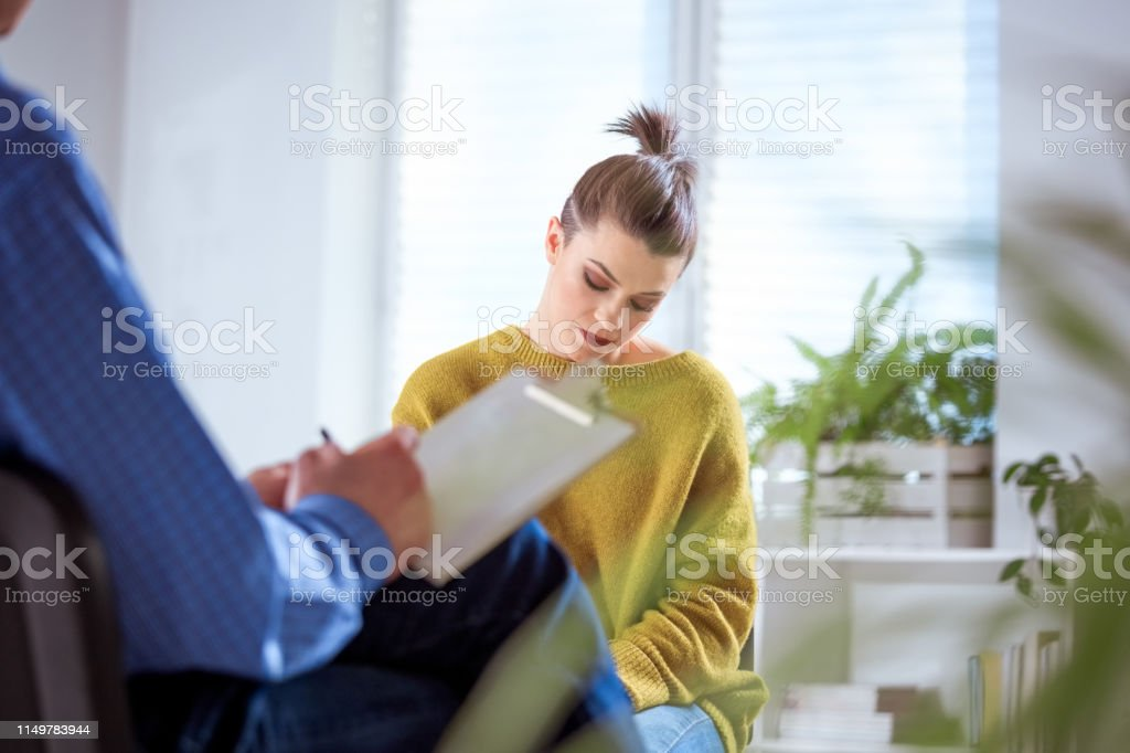 Depressed student with mental health professional Depressed young woman discussing with therapist. Female student with mental health professional in meeting during session. They are in lecture hall at university. 18-19 Years Stock Photo
