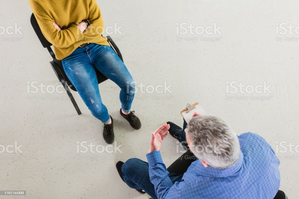 Depressed student with mental health professional High angle view of young woman discussing with therapist. Female student with mental health professional in meeting during session. They are in lecture hall at university. 18-19 Years Stock Photo