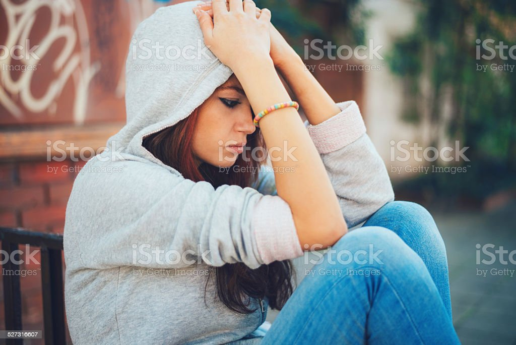 Depressed teen girl sitting lonely royalty-free stock photo