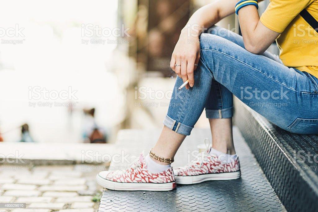 Depressed teen girl smoking on stairs stock photo