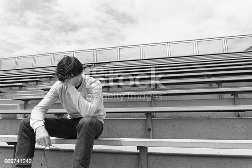 Depressed teen in bleachers.