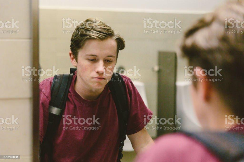 Depressed teen looks at himself in bathroom mirror stock photo