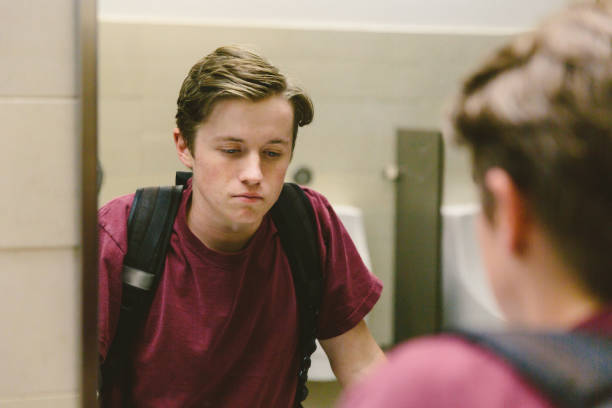 Depressed teen looks at himself in bathroom mirror stock photo