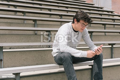 531536422istockphoto Depressed Teen on Cell Phone 669740862