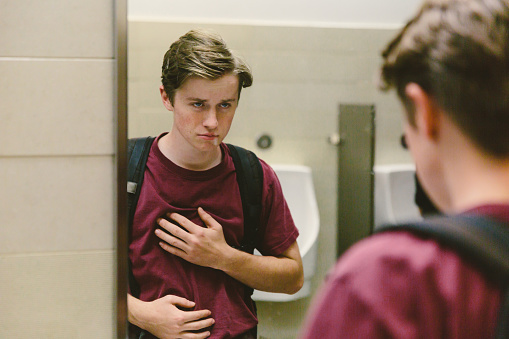 Depressed teen student looks at himself in bathroom mirror