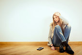 Depressed teenage girl sitting in domestic room and waiting for call.