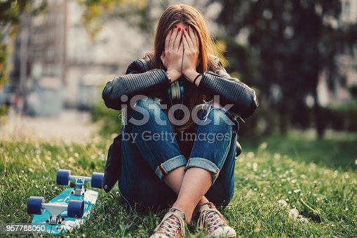 Young woman in the city park sitting on ground with head in hands