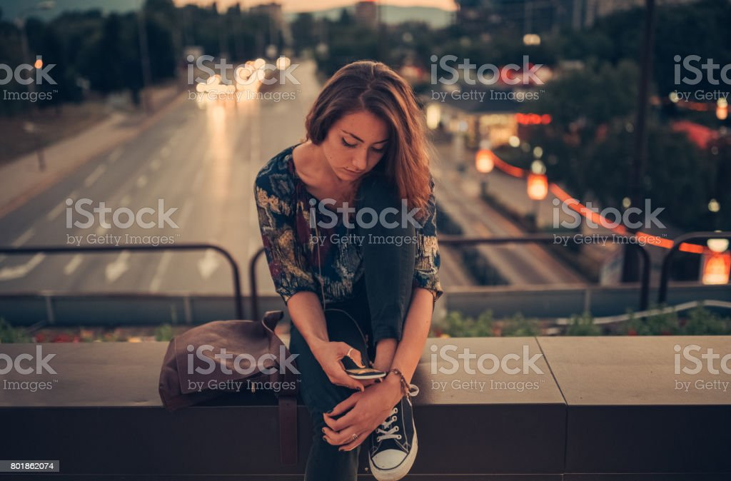 Depressed teenage girl texting on the bridge stock photo