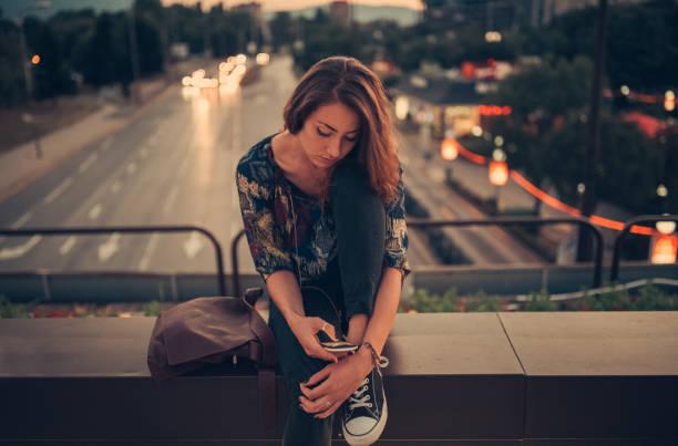 sms depressive teenager-mädchen auf der brücke - nostalgie telefon stock-fotos und bilder