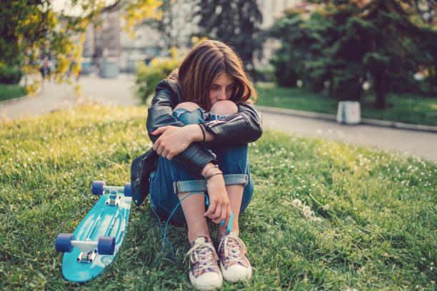 teenager-mädchen deprimiert mit skateboard in der wiese sitzen - nostalgie telefon stock-fotos und bilder