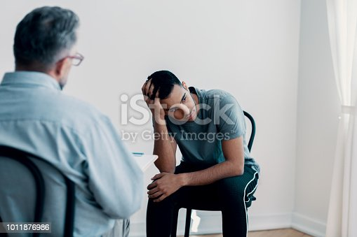 istock Depressed teenager looking away while talking to his therapist 1011876986