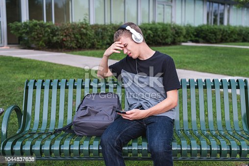 811258918 istock photo Depressed teenager sitting on bench outside of his school while listening to music with his headphones. 1044837638