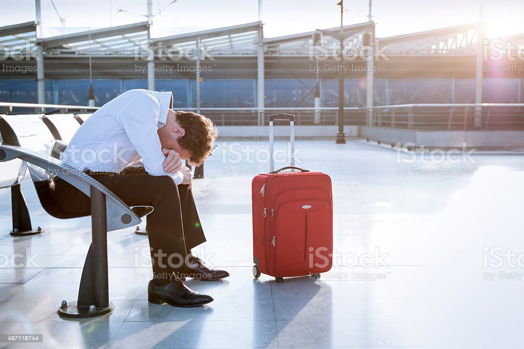 Depressed traveler waiting at airport, flights delays and cancellations stock photo