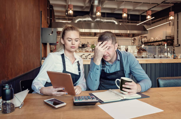 Depressed two entrepreneurs man and woman inside their restaurant overwhelmed by finance problems stock photo