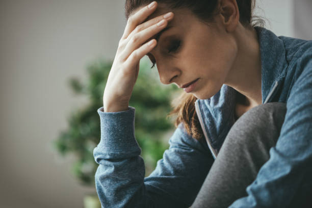 Depressed woman at home Sad depressed woman at home sitting on the couch, looking down and touching her forehead, loneliness and pain concept apprehension stock pictures, royalty-free photos & images