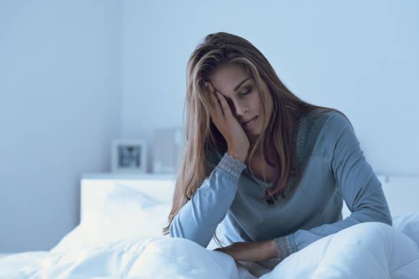 Depressiven Frau in der Nacht wach, sie ist ihre Stirn berühren und leiden unter Schlaflosigkeit – Foto