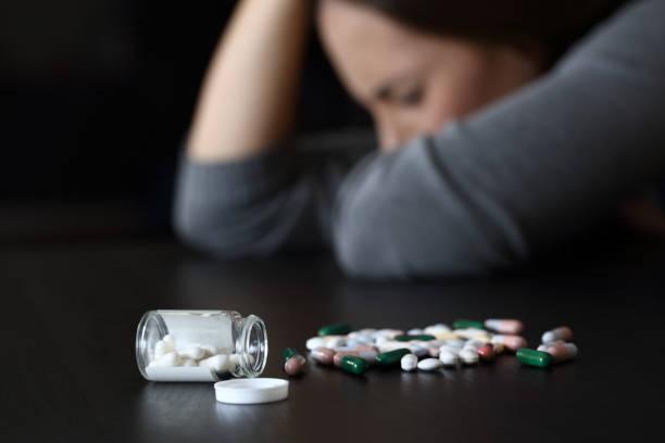 donna depressa accanto a un sacco di pillole - assuefazione foto e immagini stock