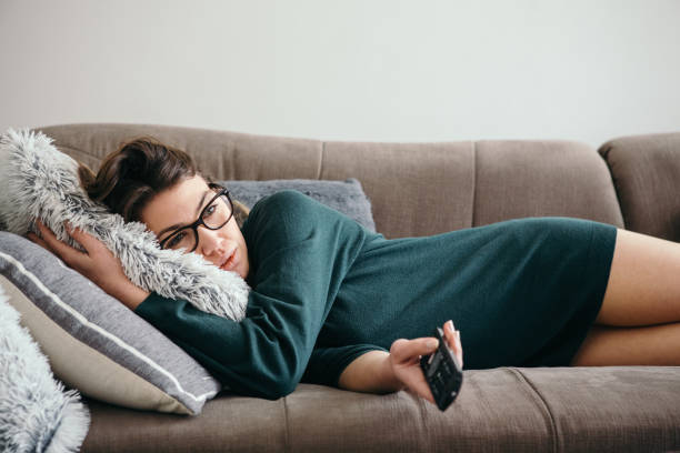 Depressed Woman Changing Channels on a TV Remote stock photo