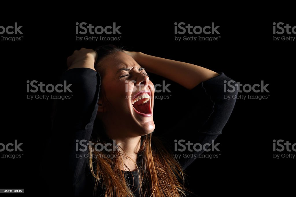 Depressed woman crying and shouting desperate in black stock photo