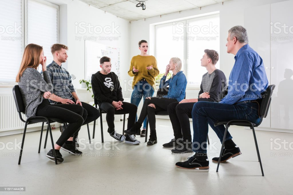 Depressed woman discussing problems in therapy Depressed woman discussing problems with friends and mature mental health professional. Social worker is with young university students in lecture hall. They are wearing casuals. 18-19 Years Stock Photo