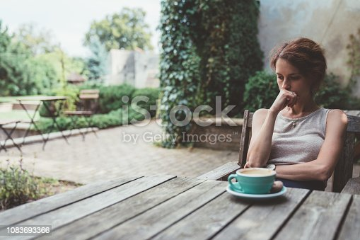 Unhappy woman sitting thoughtfully at the back yard